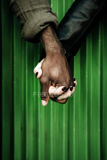 Concepto de amor interracial. Pareja de pie de la mano en la calle - foto de stock