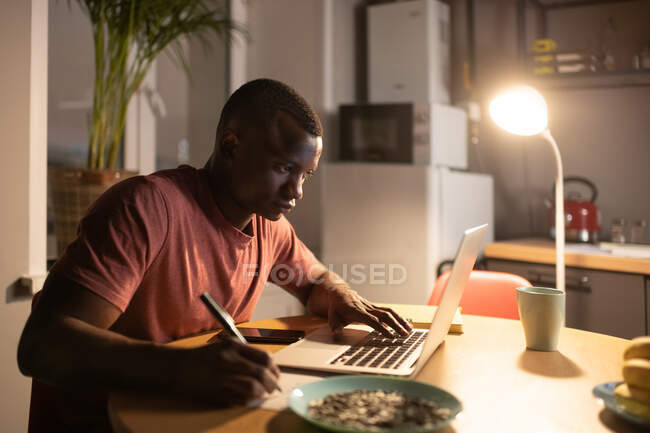 Ethnic male student browsing data on laptop and writing during studies at home — Stock Photo
