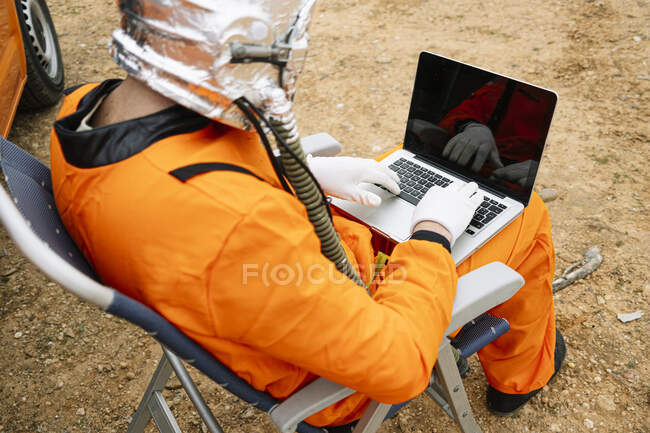 Man dressed as astronaut using laptop — Stock Photo