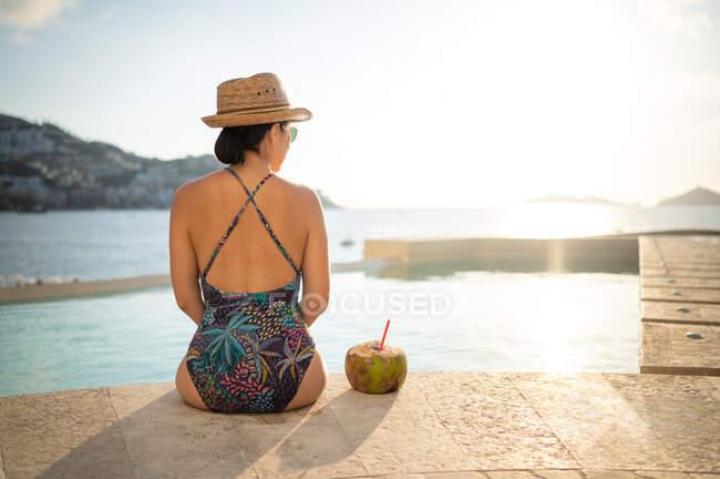 Donna felice rilassarsi in piscina e bere acqua di cocco — Foto stock