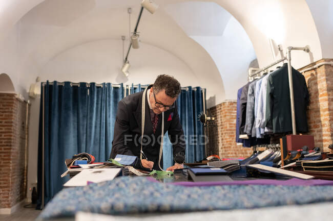 Focused senior male tailor creating sketches on table while working in loft studio — Stock Photo