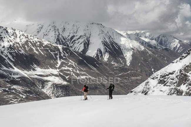 Male friends with splitboards on snowfield against mountain range during vacation — Stock Photo