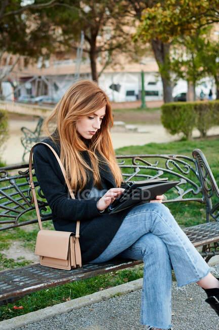 Une jolie jeune femme regardant sa tablette dans un parc — Photo de stock