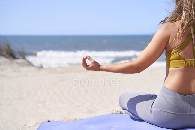 Крупным планом молодая женщина сзади делает жест медитации с закрытыми пальцами перед морем. Концепция релаксации, концентрации и мира. — стоковое фото