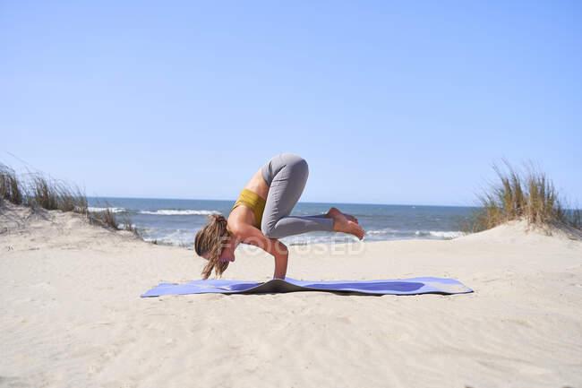 Молодая девушка, занимающаяся йогой Бакасана на пляже утром. Медитация и концепция здорового образа жизни. — стоковое фото