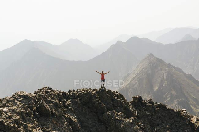 Женщина, стоящая с распростертыми руками на вершине горы против ясного неба — стоковое фото