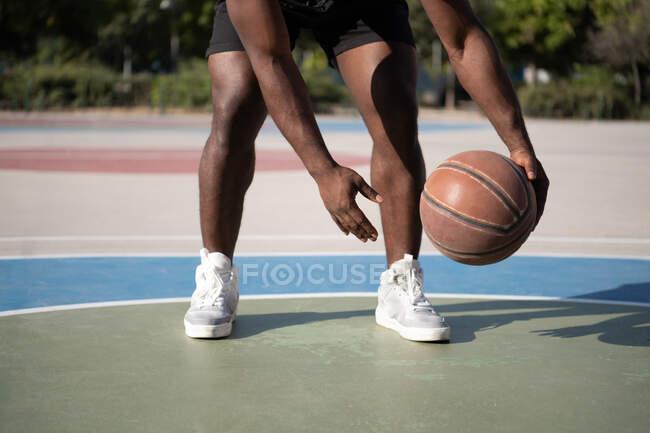 Обрезанный афроамериканец делает фристайл дриблинг на корте во время тренировки — стоковое фото