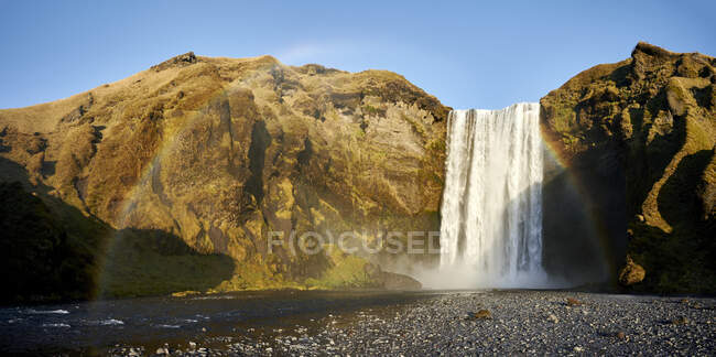 Clean waterfall on rough cliff refracting sunlight into rainbow on sunny day in countryside — Stock Photo