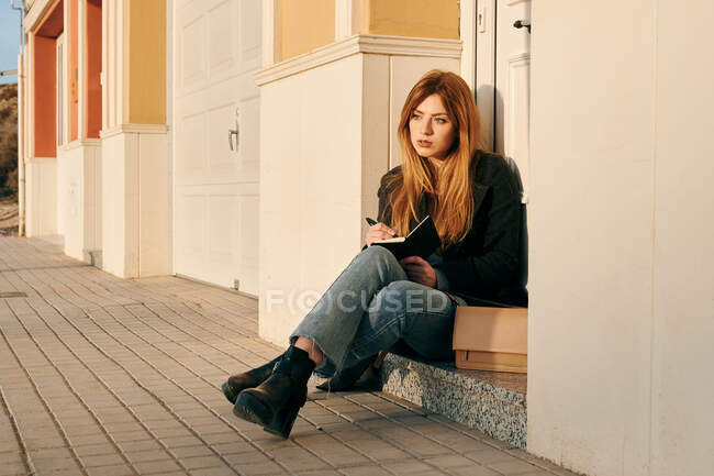 Young woman writing in her notebook while she sitting on the street — Stock Photo