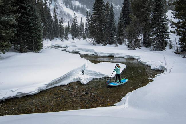 Жінка піднімається весло-посадка на річці серед снігового поля — стокове фото