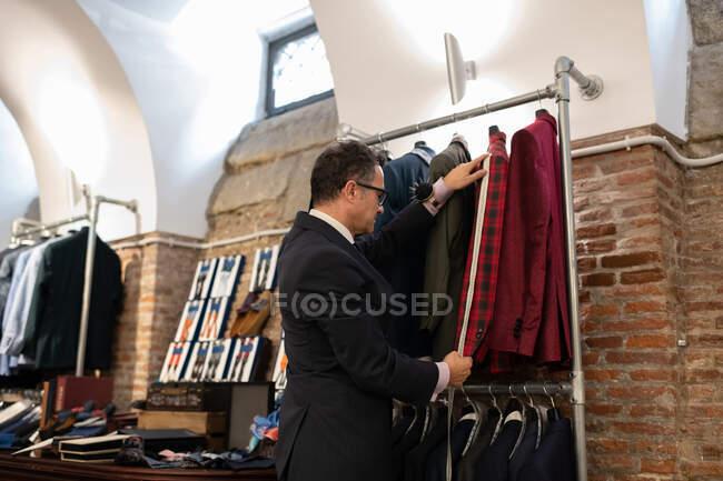 Зрілий чоловік у костюмі вимірює рукав картатої куртки на рейці для одягу в студії. — стокове фото