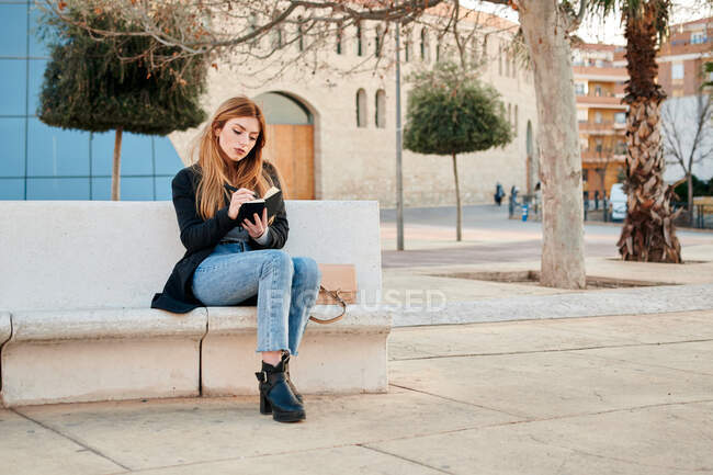 Young woman writing in her notebook sitting on a stone bench — Stock Photo