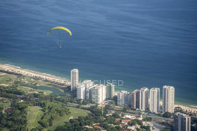 Bella vista al parapendio sorvolando edifici residenziali, aree verdi e l'oceano, visto da Pedra Bonita rampa di volo gratuito, Parco Tijuca, Rio de Janeiro, Brasile — Foto stock