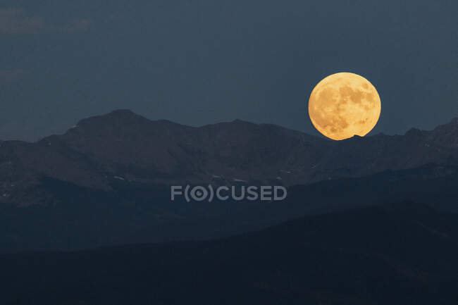Idyllic shot of full moon over mountain range against clear sky at dusk — Stock Photo