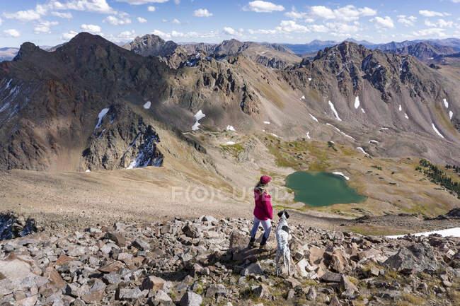 Женщина в походе с собакой на горе во время отпуска — стоковое фото