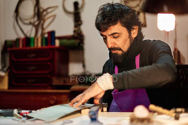 Крефтсмен вирізає металеву пластину пилкою за робочим столом. — стокове фото