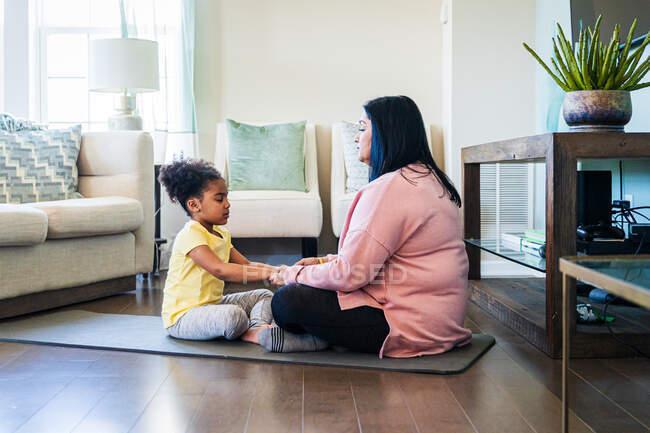 Бабуся медитує з внучкою, сидячи вдома на маті у вітальні. — стокове фото