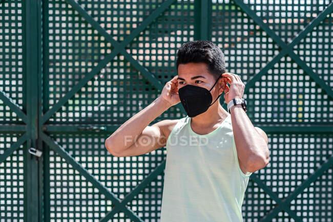 Retrato de atleta latinoamericano poniéndose una mascarilla. - foto de stock