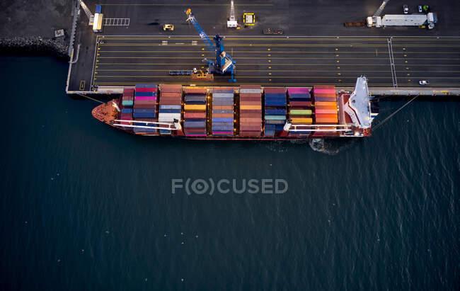 Desde arriba del buque de carga moderno con contenedores de colores amarrados en muelle de carga pavimentada en el puerto de la ciudad - foto de stock