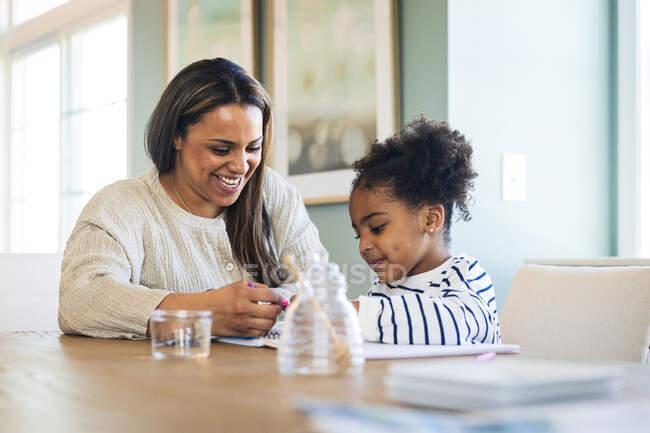 Счастливая мать преподает рисование дочери, сидя за столом — стоковое фото