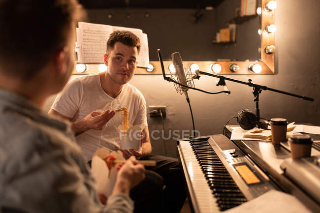 Man eating delivery noodles during lunch with colleague in recording studio — Stock Photo