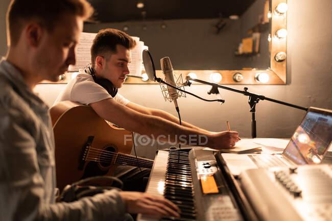 Guitarrista masculino haciendo notas mientras escribe una canción con un amigo en un estudio moderno - foto de stock