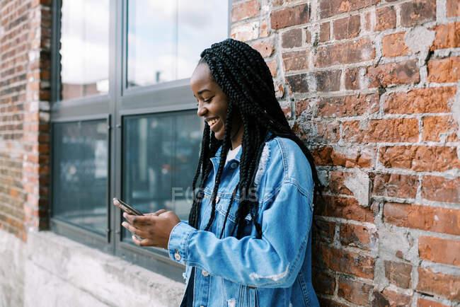 Giovane donna nera scorrendo sui social media e tenendo il telefono — Foto stock