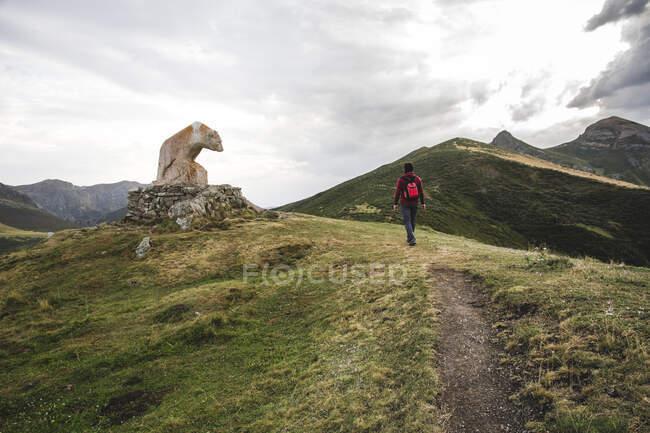 L'uomo che cammina sulla montagna accanto a portare la statua in un belvedere dei Picos de Europa — Foto stock
