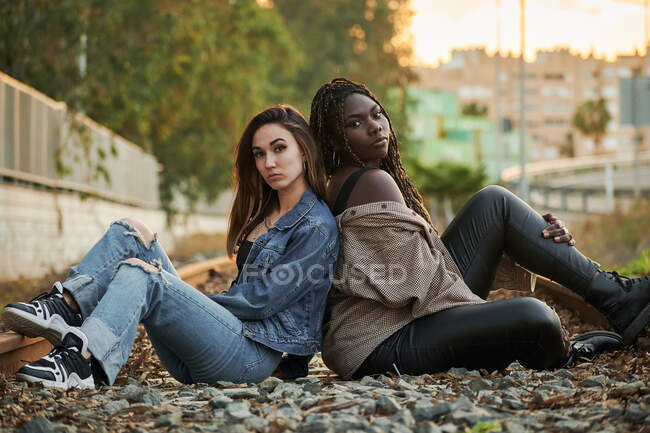 Dos jóvenes multiétnicas posando y mirando a la cámara al atardecer - foto de stock