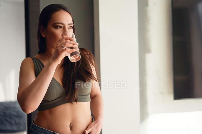Brunette boit de l'eau tout en se tenant près de la fenêtre — Photo de stock