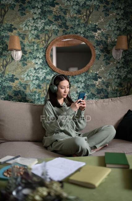 Азійка, яка слухає музику і дивиться мобільний телефон, відпочиваючи на дивані. — стокове фото