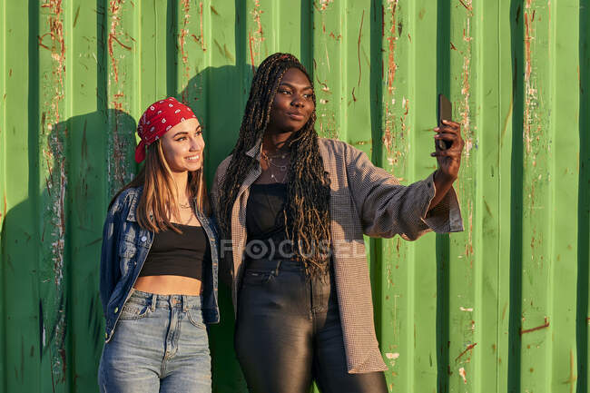 Dos mujeres multiétnicas con ropa urbana tomando una foto con un teléfono - foto de stock