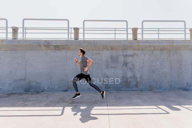 Perfil vista de jovem correndo ao ar livre na frente de uma parede — Fotografia de Stock