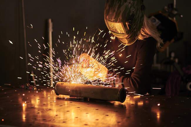 Female mechanic in protective helmet welding pieces — Stock Photo