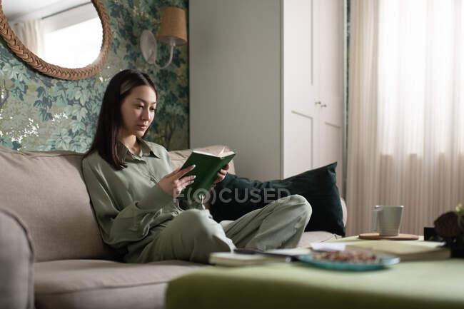 Молода азіатка відпочиває на дивані і читає книжку на вихідних вдома. — стокове фото