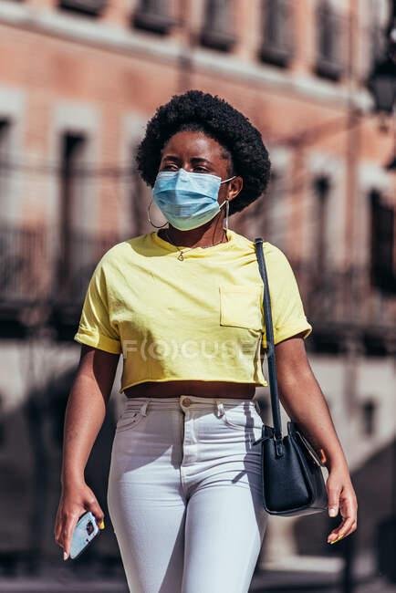 Menina afro-americana com máscara facial andando por uma rua da cidade. — Fotografia de Stock