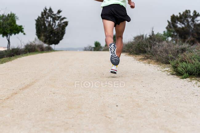 Вид сзади на ноги бегуна, тренирующегося на тропе в лесу. — стоковое фото