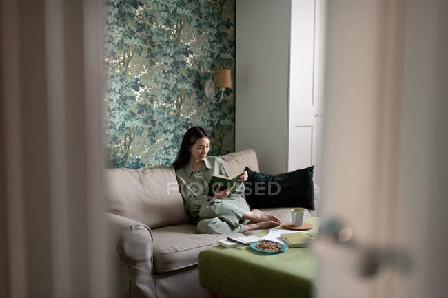 Азійка відпочиває на дивані і читає книжку в елегантній вітальні вдома. — стокове фото