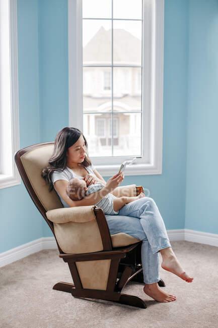 SMS auf dem Smartphone in den sozialen Medien. Chinesische Asiatin mit neugeborenem Säugling und Chat auf dem Smartphone. Kommunikation mit Freunden zu Hause. — Stockfoto