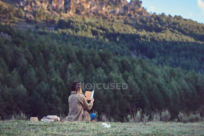 Mujer en la montaña leyendo un libro - foto de stock