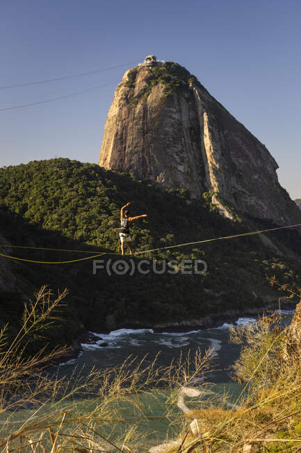 Bella vista all'uomo che cammina sulla Highline con Sugar Loaf Mountain sul retro, Rio de Janeiro, Brasile — Foto stock