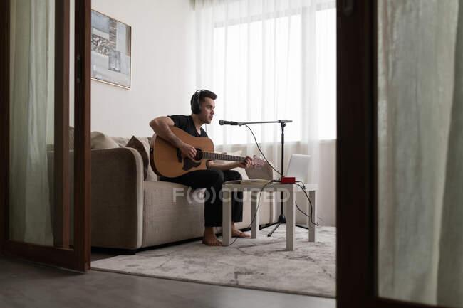 Чоловік грає на гітарі та співає пісню, сидячи на дивані під час репетицій вдома. — стокове фото