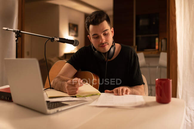 Male musician reading notes and writing in planner while creating song at home — Stock Photo