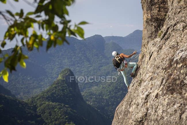 Bella vista al climber femminile sulla ripida montagna della foresta pluviale rocciosa, Parco Tijuca, Rio de Janeiro, Brasile — Foto stock