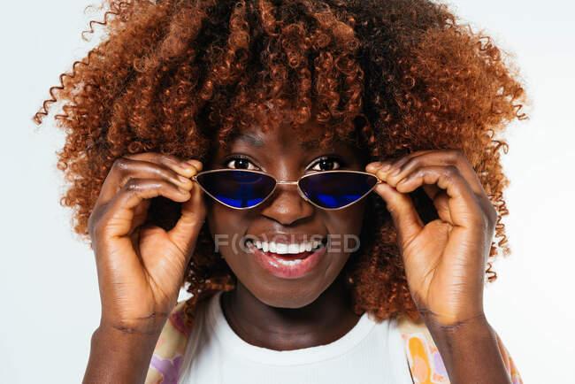 Black young woman wearing sunglasses looking at camera — Stock Photo