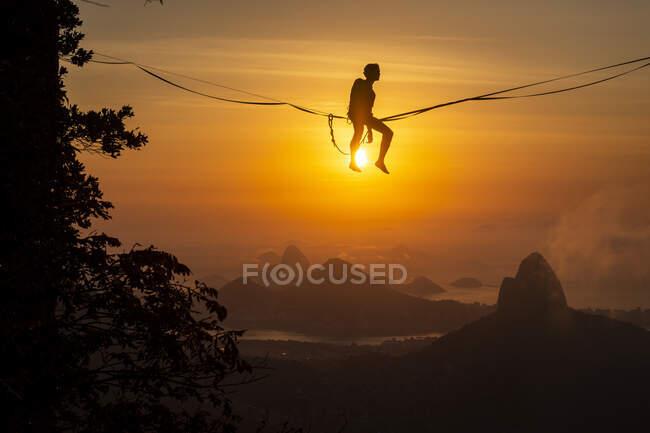 Bella vista alla silhouette highliner maschile sopra il sole sul paesaggio montano, Rio de Janeiro, Brasile — Foto stock