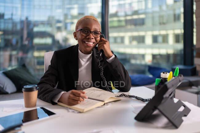Керівниця чорних жінок посміхається і розмовляє по телефону під час роботи в офісі. — стокове фото