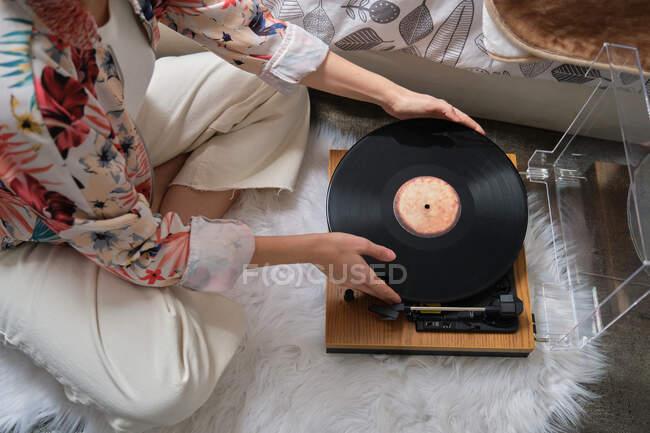 Unerkennbare Frau legt Schallplatte auf Plattenspieler — Stockfoto