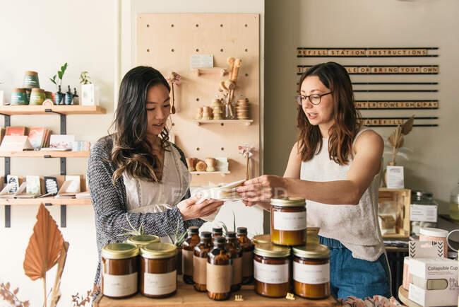 Клієнт і власник магазину шукають продукти в стильній крамниці. — стокове фото