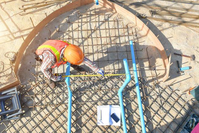 Технік з рівнем вимірювання під час роботи, будівельник вимірює опорні балки під час заходу сонця. — стокове фото